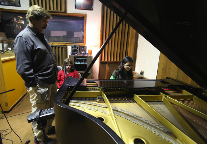Gabriella Orton playing the piano at Fame Studios with Rick Hall looking on.